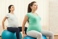 Красивые беременные женщины делая йогу на шариках Стоковое фото RF