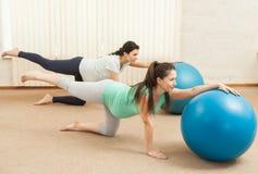 Красивые беременные женщины делая йогу на шариках Стоковое Фото