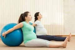 Красивые беременные женщины делая йогу с шариком Стоковое фото RF