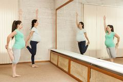 Красивые беременные женщины делая йогу Стоковые Фото
