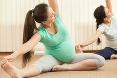 Красивые беременные женщины делая йогу Стоковое Изображение RF