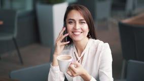 Красивые беседы девушки на кофе телефона, смеяться и выпивать в кафе, замедленном движении сток-видео