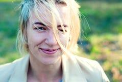 Красивые белокурые улыбки девушки в заходе солнца Стоковое Изображение