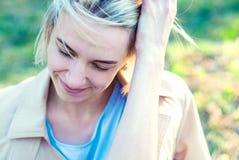 Красивые белокурые улыбки девушки в заходе солнца Стоковая Фотография