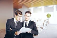 Красивые бизнесмены обсуждая контракт Стоковые Фотографии RF
