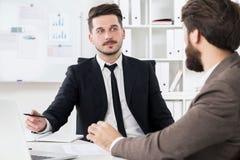 Красивые бизнесмены обсуждая что-то Стоковые Изображения