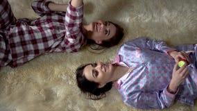 Красивые близнецы сестер в пижамах лежат на мягком ковре смотря на один другого и имея прекрасную выравниваясь беседу отношение акции видеоматериалы