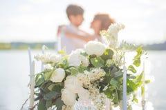 Красивые букет и свечи для свадебной церемонии на предпосылке пожененной пары на береге моря Стоковое фото RF
