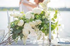 Красивые букет и свечи для свадебной церемонии на предпосылке пожененной пары на береге моря Стоковая Фотография