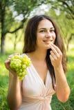Красивые виноградины дегустации девушки в саде Стоковые Фото