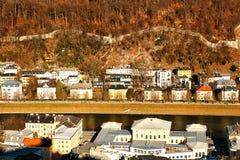 Красивые виды традиционных домов в ряд рядом с рекой на ноге горы в австрийском городе  Стоковые Фото