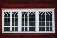 Красивые втройне белые окна на красном деревянном здании стоковое изображение rf