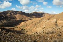Красивые вулканические горы и дорога на наклоне горы Дорога от Ла обстроганного к Betancuria Фуэртевентура Стоковое фото RF