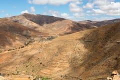 Красивые вулканические горы и дорога на наклоне горы Дорога от Ла обстроганного к Betancuria Фуэртевентура Стоковое Изображение