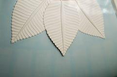 Красивые высекаенные листья с штриховатостями бетона, камня, гипса на голубом цементе покрасили потолок текстура Стоковое Изображение