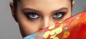 Красивые глаза и макияж девушки рядом с покрашенной тканью шелка стоковое изображение rf