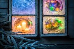 Красивые горящие свечи для рождества в замороженном окне на кануне Стоковая Фотография RF