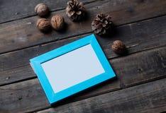 Красивые голубые рамка, гайки и конусы лежа на чудесной древесине Стоковые Изображения