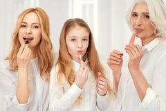 Красивые 3 дамы прикладывая состав губы совместно Стоковое фото RF