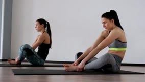 Красивые девушки выполняют тренировку для позиции сидя в позиции бабочки Pilates йога дыхание глубоко Метод  акции видеоматериалы