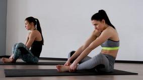 Красивые девушки выполняют тренировку для позиции сидя в позиции бабочки Pilates дыхание глубоко сток-видео