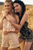 Красивые девушки в вскользь одеждах представляя на сене Стоковое Изображение