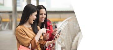 Красивые девушки держа хозяйственные сумки используя умный телефон Стоковые Изображения RF