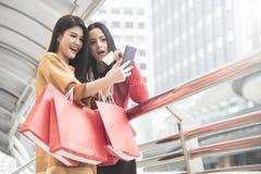 Красивые девушки держа хозяйственные сумки используя умный телефон Стоковое фото RF