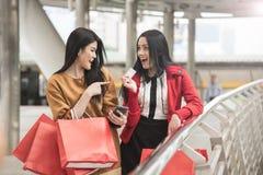 Красивые девушки держа хозяйственные сумки используя умный телефон Стоковые Фото