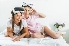 красивые девушки имея потеху с шлемофонами виртуальной реальности Стоковые Фотографии RF