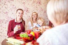 Красивые девушки и ребёнок сидя на праздничной таблице на домашней предпосылке Семья усмехаясь на рождественском ужине Стоковое Изображение RF