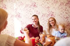 Красивые девушки и ребёнок сидя на праздничной таблице на домашней предпосылке Семья усмехаясь на рождественском ужине Стоковое фото RF