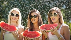 Красивые девушки с солнечными очками есть свежий арбуз и улыбки Счастливая молодая женщина есть арбуз в парке образ жизни молодос Стоковое Изображение RF