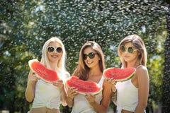 Красивые девушки с солнечными очками есть свежий арбуз и улыбки Счастливая молодая женщина есть арбуз в парке образ жизни молодос Стоковые Фотографии RF