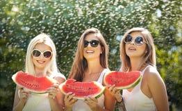 Красивые девушки с солнечными очками есть свежий арбуз и улыбки Счастливая молодая женщина есть арбуз в парке образ жизни молодос Стоковые Изображения RF