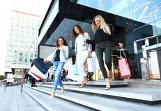 Красивые девушки с хозяйственными сумками идя на мол Стоковые Фотографии RF