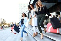 Красивые девушки с хозяйственными сумками идя на мол Стоковое Изображение