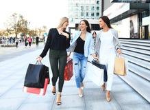 Красивые девушки с хозяйственными сумками идя на мол Стоковое Фото