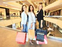Красивые девушки с хозяйственными сумками идя на мол Стоковое фото RF