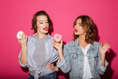 Красивые 2 друз женщин есть donuts Стоковые Изображения