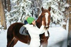Красивые девушка и лошадь в зиме стоковые фото