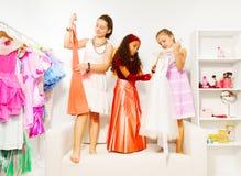 Красивые девушки выбирают платья стоя на софе Стоковые Изображения