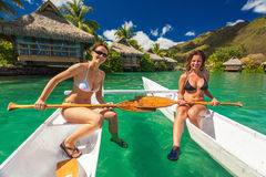 Красивые девушки в бикини ослабляя на каное на тропическом re стоковое изображение