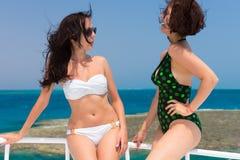 Красивые девушки в купальнике стоя на яхте на солнечной сумме Стоковая Фотография