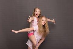 Красивые 2 девушки в розовых пижамах играют перед идти положить в постель Стоковое фото RF