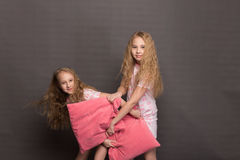 Красивые 2 девушки в розовых пижамах играют перед идти положить в постель Стоковая Фотография RF