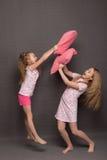 Красивые 2 девушки в розовых пижамах играют перед идти положить в постель Стоковое Изображение RF