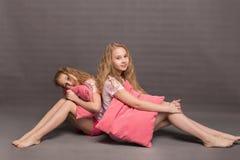 Красивые 2 девушки в розовых пижамах играют перед идти положить в постель Стоковые Фотографии RF