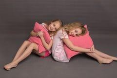 Красивые 2 девушки в розовых пижамах играют перед идти положить в постель Стоковые Изображения