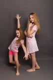 Красивые 2 девушки в розовых пижамах играют перед идти положить в постель Стоковое Фото